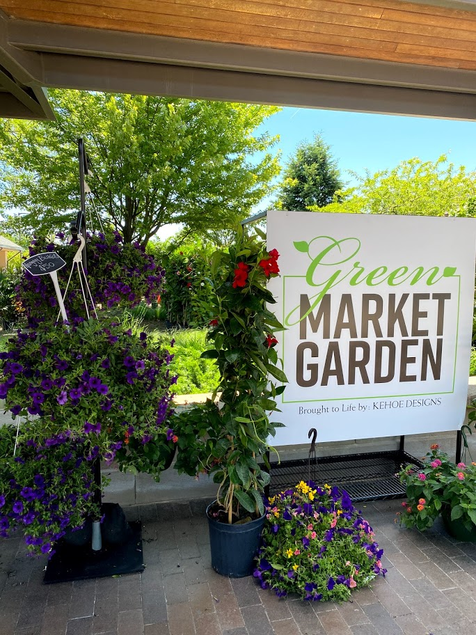 """White sign that says """"Green Market Garden"""" standing between small purple and yellow flower arrangements"""