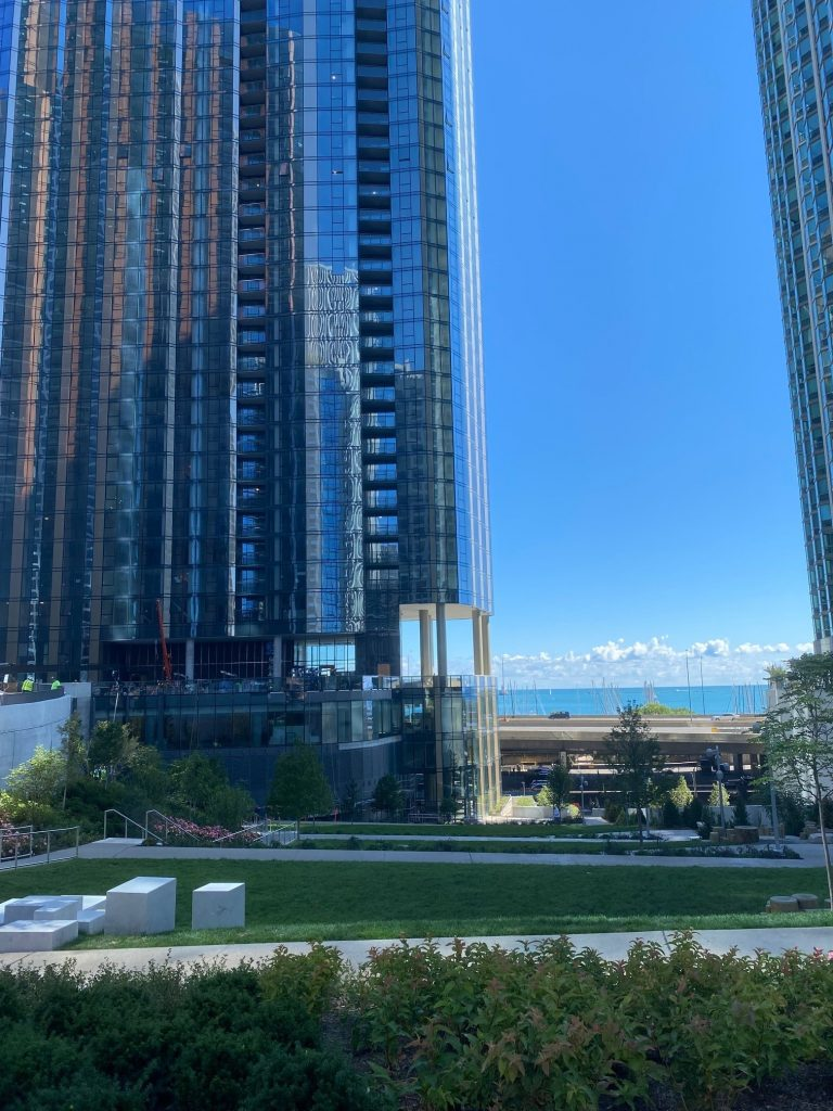 Cascade Park at the base of luxury high rise residences in Lakeshore East neighborhood in Chicago with Lake Michigan in the background and small bushes in the foreground