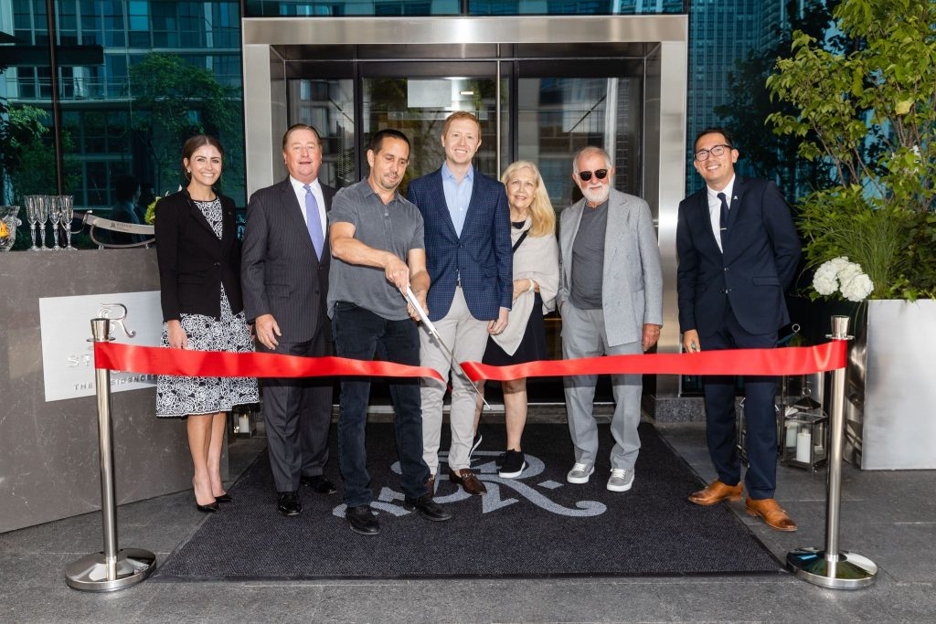 Seven people in formal attire cut a celebratory ribbon in front of The Residences at St. Regis Chicago.