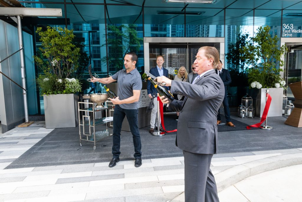 A man in a suit performs a sabrage with a champagne bottle at the celebratory ribbon cutting at The Residences at St. Regis Chicago.