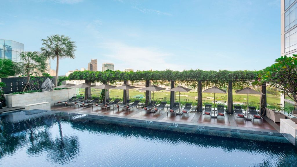 The terrace of the St. Regis Bangkok hotel with a pool and pool deck with lounge chairs.